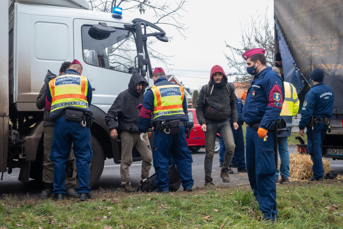 A Készenléti Rendőrség munkatársai sorra átvizsgálják az egy román állampolgár által vezetett, magyar rendszámú teherautóban talált ötvenkilenc migránst Kiskunhalas belterületén 2020. december 19-én.