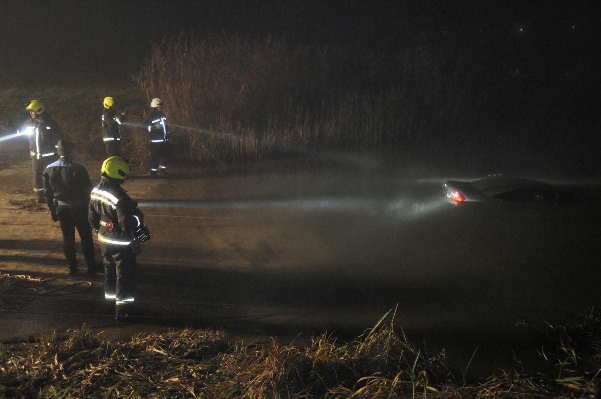 Tűzoltók vontatnak ki búvárok segítségével egy autót a Dunából a soroksári kompnál 2021. január 9-én. A jármű vezetője a Soroksárról Csepel felé tartó kompra akart felhajtani. Az autó a Dunába gurult és elmerült, a három utas ki tudott szállni.