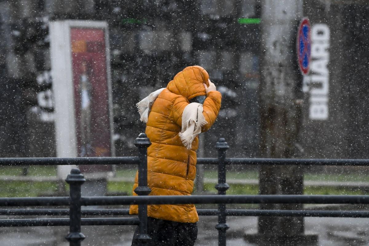 Kapucniját fogja egy nő Debrecenben, az erős széllel kísért havas esőben 2021. január 25-én.