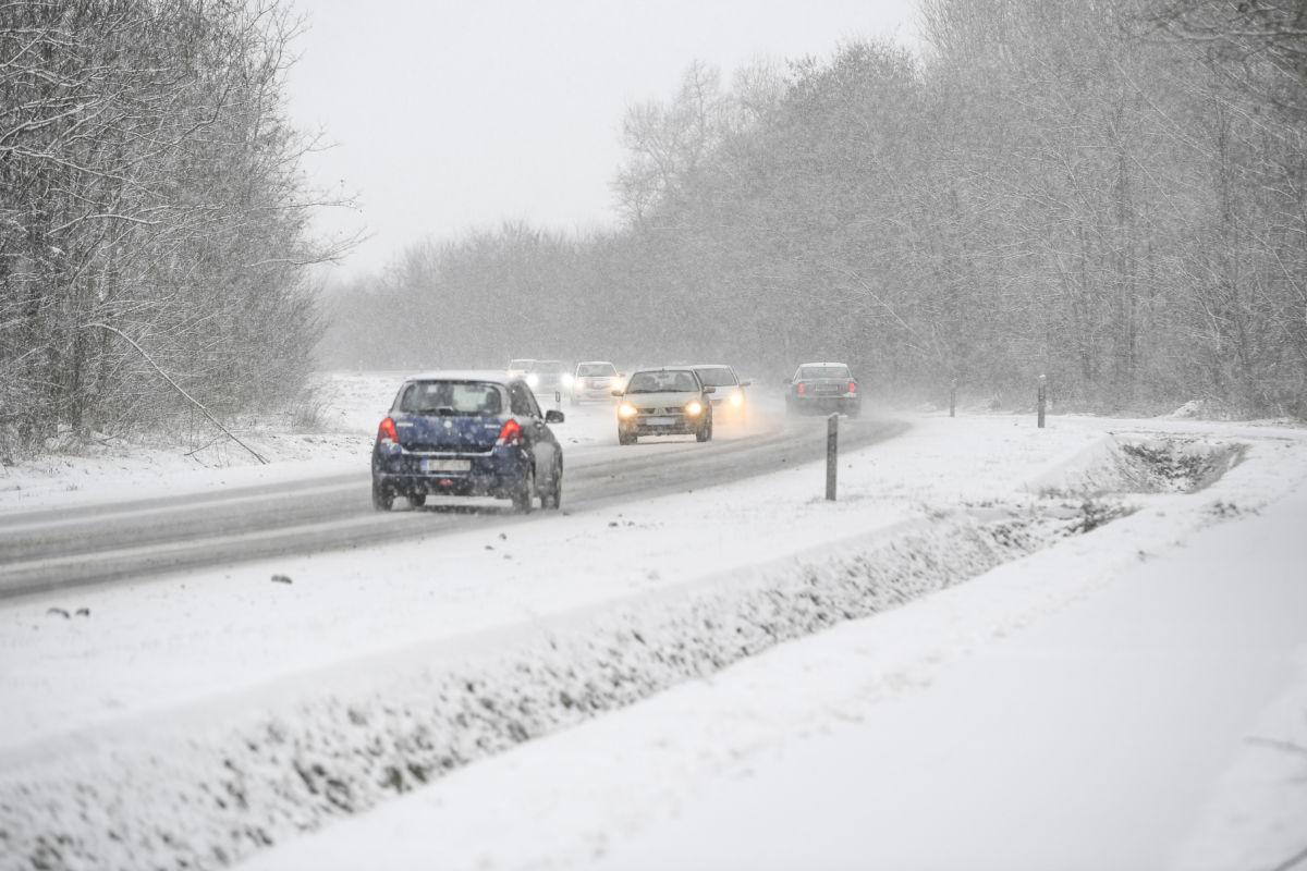 Járművek haladnak a sűrű hóesésben a 471-es főúton Nyíradony közelében 2021. január 15-én.