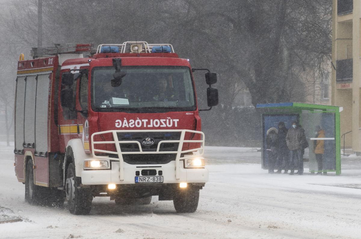 Tűzoltóautó és buszmegállóban várakozó utasok hóviharban Nyíregyházán, a Sóstói úton 2021. február 11-én.