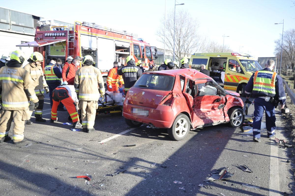 Hordágyon visznek egy sebesültet a mentőautóhoz a Ferihegyi Repülőtérre vezető úton, ahol három személyautó és egy kisteherautó ütközött össze 2021. március 3-án.