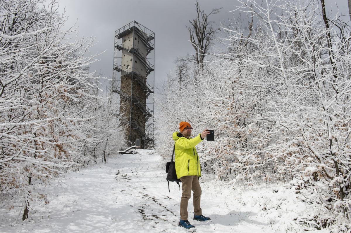 Férfi a havas úton Galyatetőn, háttérben a kilátó 2021. április 6-án.