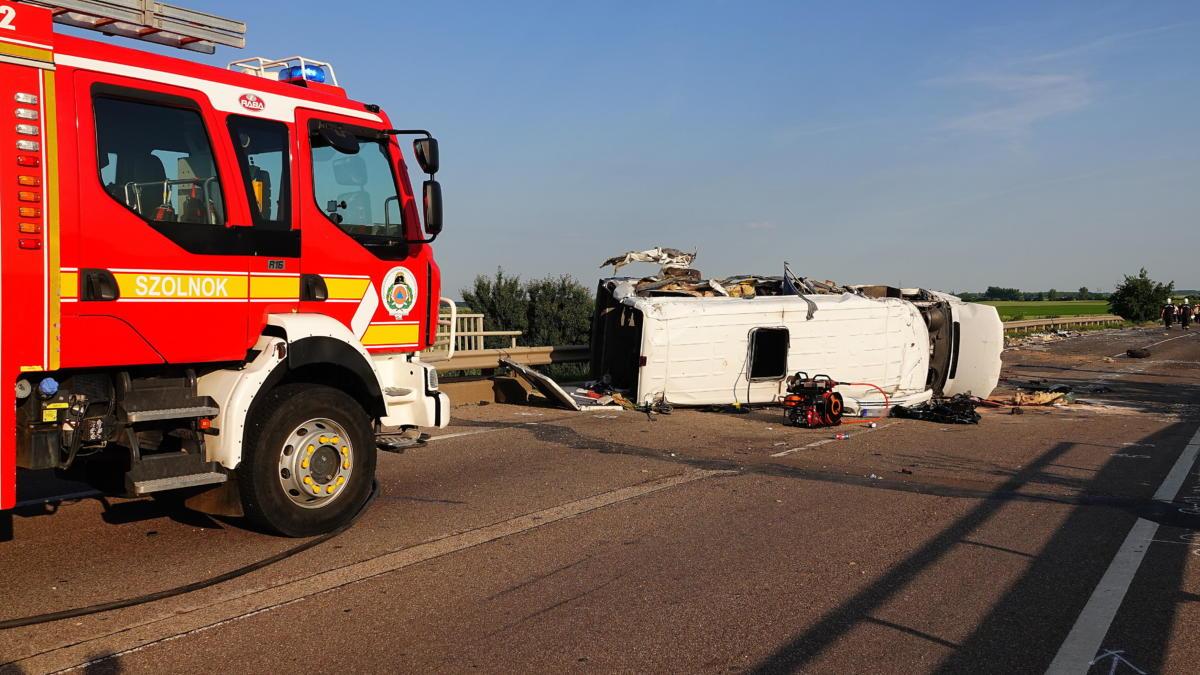 Ütközésben összetört kisbusz a 4-es főút 92-es kilométerénél, Szolnoknál 2021. június 4-én. A jármű egy kamionnal ütközött össze. A balesetben hárman meghaltak és tizenhárman megsérültek.