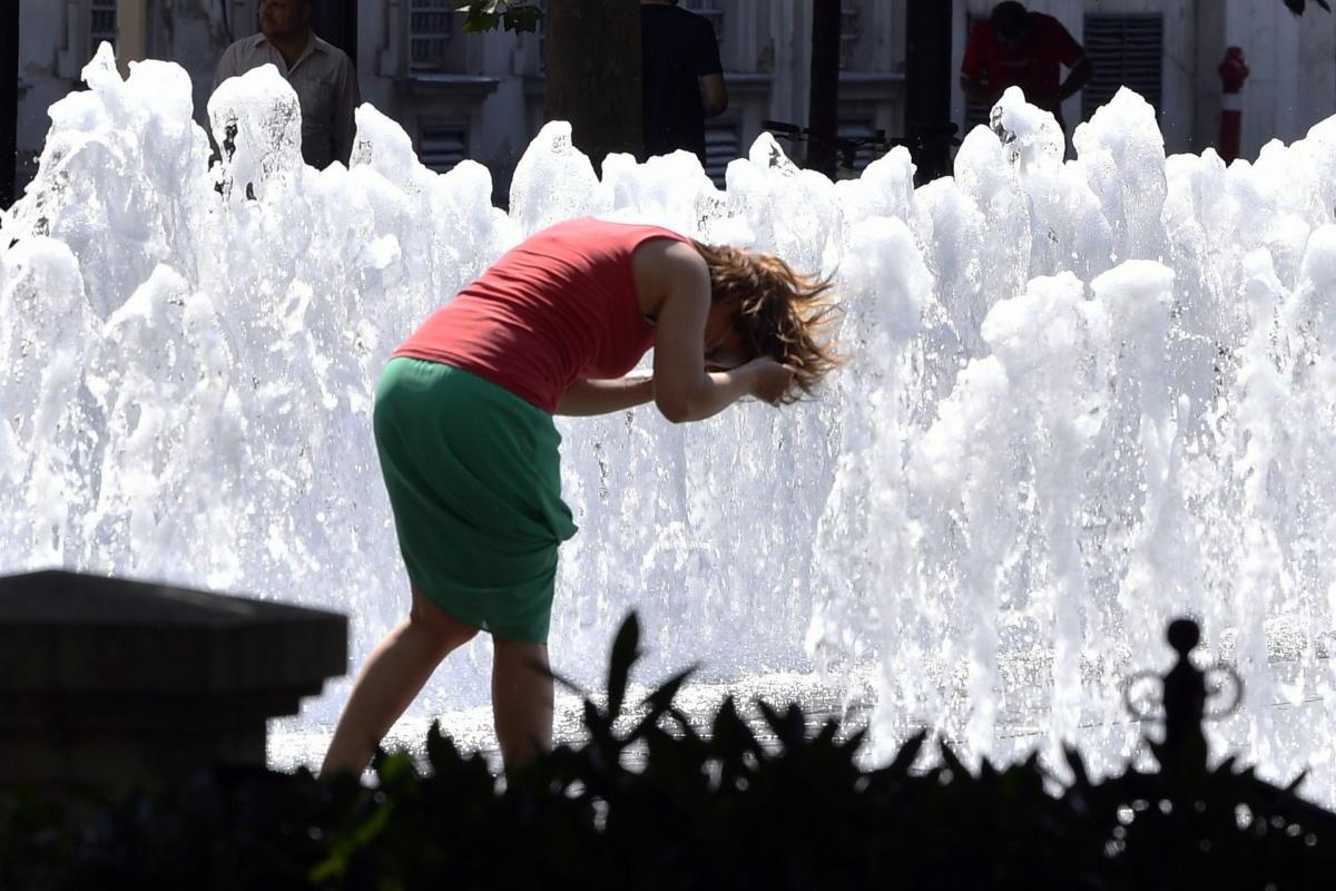 Egy nő bevizezi magát a hőségben a Szabadság téri szökőkútban 2021. június 19-én. Ezen a napon életbe lépett az országos tisztifőorvos által elrendelt hőségriasztás.