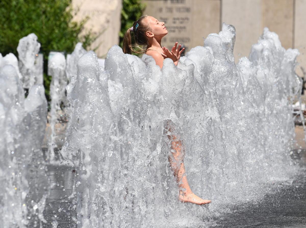 Egy kislány játszik a szökőkútnál a kánikulában a Szabadság téren 2021. június 22-én.