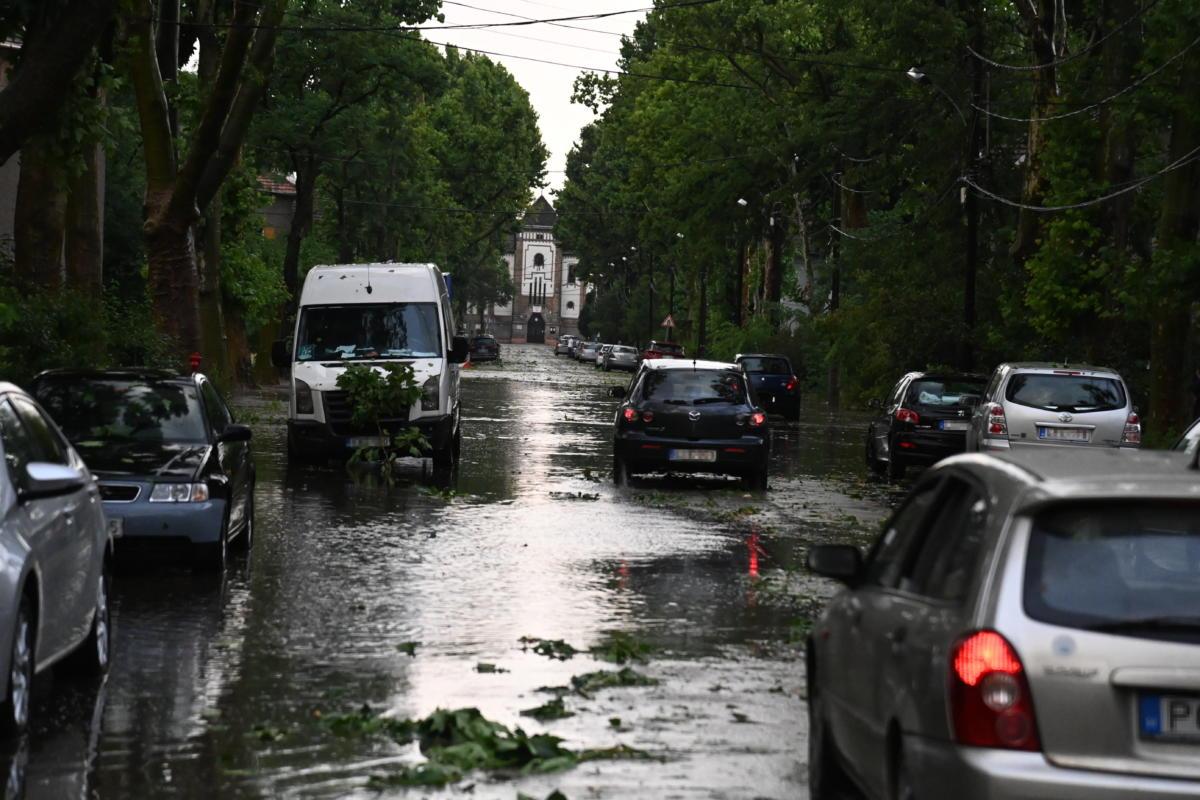 Autók haladnak a felhőszakadás után esővízzel elárasztott, letört faágakkal teli úton Budapesten, Wekerletelepen 2021. július 9-én.