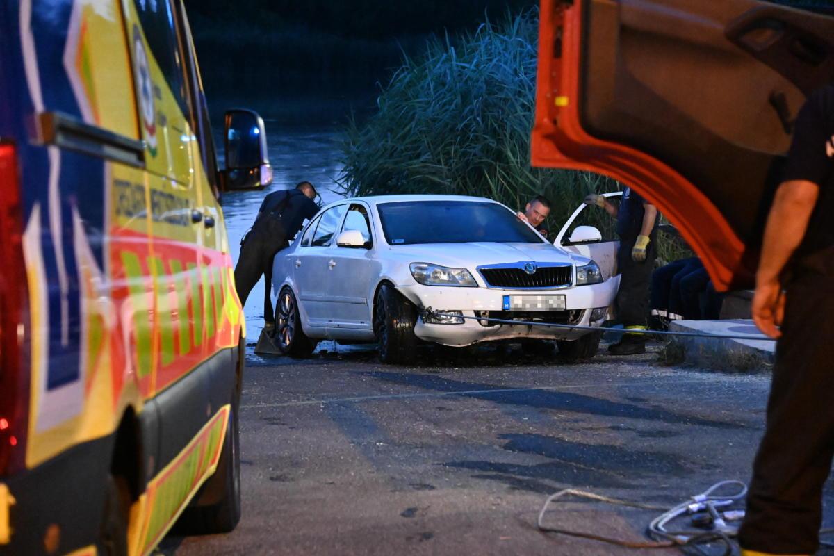 Tűzoltók vontatnak ki egy személygépkocsit a Dunából Csepelen, a Hollandi útnál, a kompkikötő közelében 2021. július 9-én.