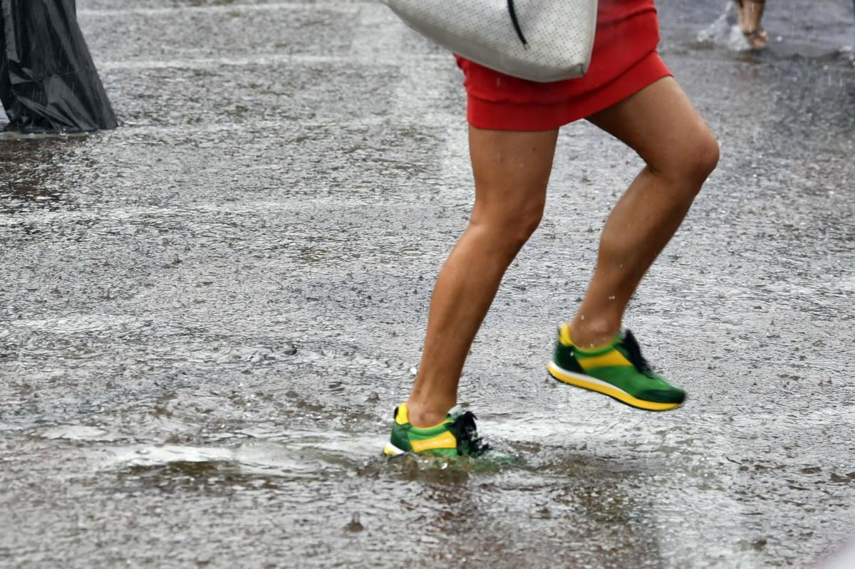 Gyalogos a felhőszakadás miatt felgyülemlett esővízben, az esztergomi Széchenyi téren 2021. augusztus 5-én.